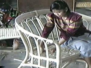 Tissage autour de la carcasse en rotin d'un canapé